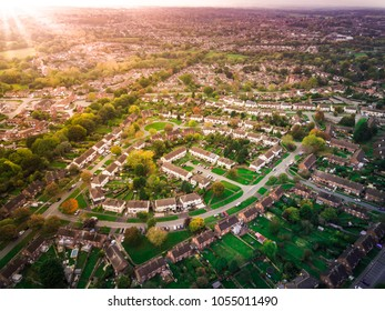 Sunrise above a British housing estate with fields and hills in the background. Dramatic lighting and warm colours give a homely effect.