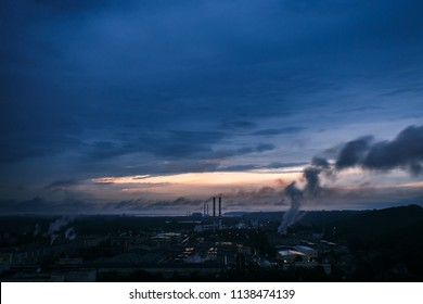 Sunrise above cardboard and paper mill. Lots of fumes and clouds. Air pollution and industrial district at cloudy sunrise.