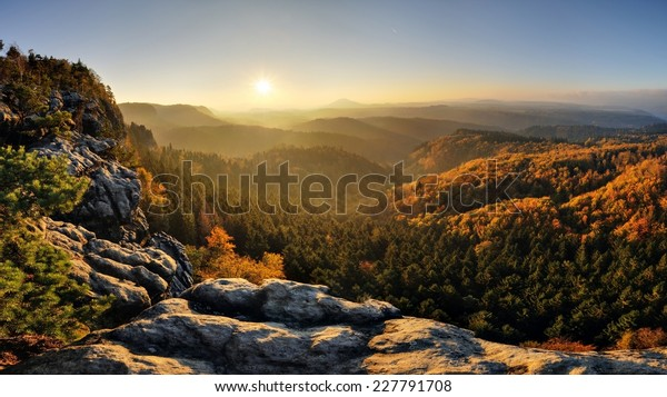 Sunrise above the deep autumn valley of national park Bohemian Switzerland
