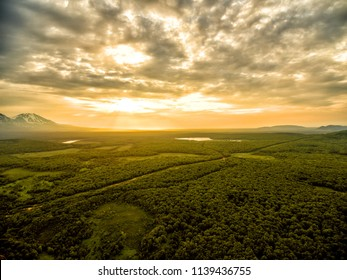 Sunrise above forest on Kamchatka in cloudy day