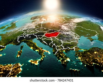 Sunrise above Hungary highlighted in red on model of planet Earth in space with visible country borders. 3D illustration. Elements of this image furnished by NASA.