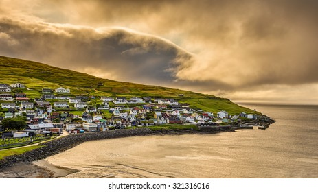Sunrise above the village of Sandavagur with heavy clouds, Faroe Islands, Denmark. Hdr processed.