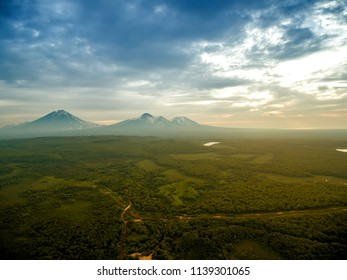 Sunrise above volcano on Kamchatka in cloudy day