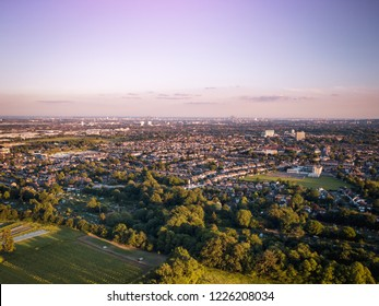 Sunrise aerial view of houses in London above a London housing estate next to countryside and farm land. Fields and community housing can be seen in the foreground