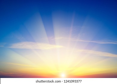 Sunrise against blue sky and white clouds
