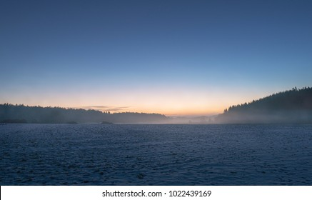 Sunrise at a agricultural field with dense fog in the distance, clear cold sky. Sweden