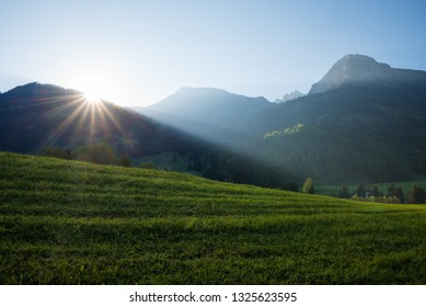sunrise at allgau alps, sun is coming over the mountain crest. dark grassland and blue clear sky.