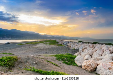 Sunrise along the Palisadoes peninsula in Kingston, Jamaica with large rock boulders to help prevent flooding on the strip of land.