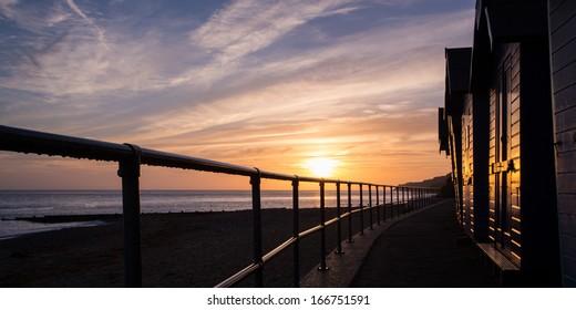 Sunrise along a row of beach huts at Cromer on the North Norfolk coast