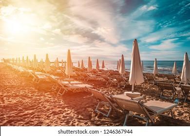 Sunrise of amazing beach with white umbrellas and turquoise sea.
