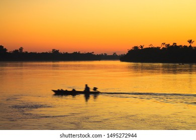 Sunrise in the Amazon Rainforest, looking towards the Nanay River. In the background a person in his boat, starting his daily journey.
