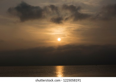 Sunrise among gray clouds in the sky above the sea