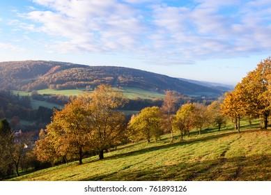 Sunrise in Ardennes, Wallonia, Belgium. Trees on a grass hill with valley in background. Autumn fall season. Colorful leaves. Belgian countryside.
