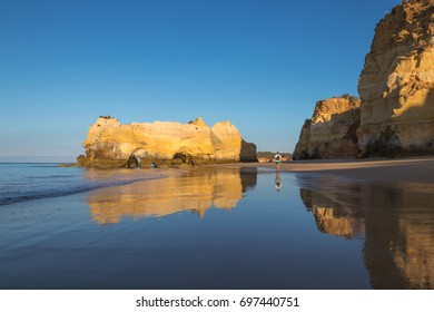 Sunrise at the beach in Algarve, Portugal, with rocks reflected in the water.