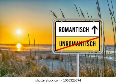 Sunrise at Beach with german street sign romantic and no unromantic. Romantisch und unromantisch.