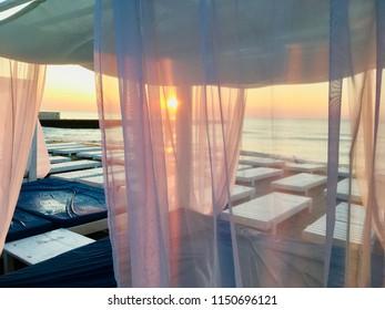 Sunrise in beach sea. Sun beds and bungalows on the beach.
