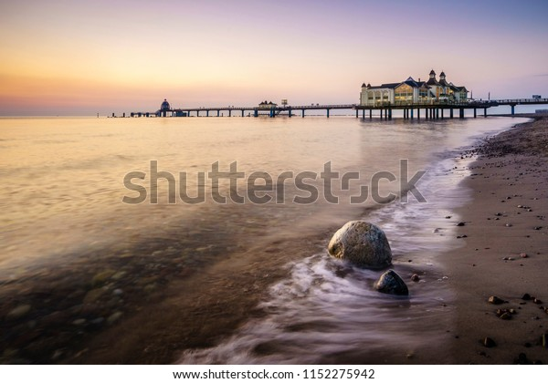 Sunrise at the beach in Sellin with the wooden pier at the background and a rock in the foreground.