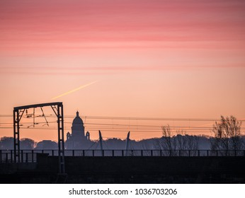 Sunrise behind Ashton Memorial Lancaster UK with Electric Rail cables in foreground