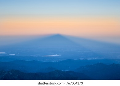 Sunrise behind a mountain peak with its shadow projected over the valley, in the Alps between Switzerland (Valais) and Italy