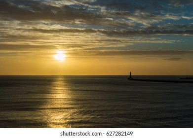 Sunrise behind Roker Lighthouse L in Sunderland England horizontal photography