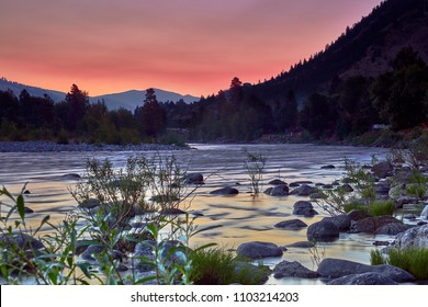 Sunrise at a bend in the Wenatchee River during fire season with an orange sky in the summer