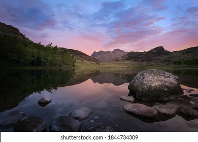 Sunrise at Blea Tarn in Lake District, UK.Idyllic morning landscape scene.Sky with colourful clouds at dawn, mountain range and trees on lakeshore reflecting in calm water surface of lake with stones.