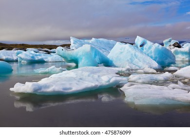 Sunrise. Blue and emerald icebergs and ice floes are reflected in smooth water of the Gulf Yokulsarlonin Iceland