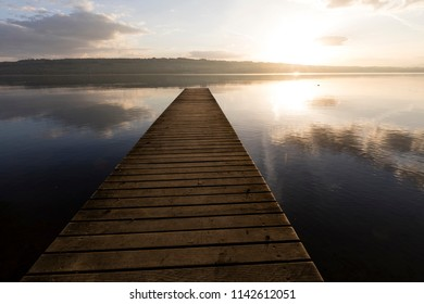 Sunrise with a boardwalk at Lake Sempach in Switzerland.