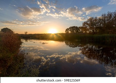 Sunrise by the river, Russia. The bright rays of the sun lit up the watery surface of the river.