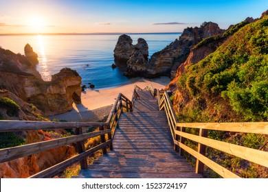Sunrise at Camilo beach in Lagos, Algarve, Portugal. Wooden footbridge to the beach Praia do Camilo, Portugal. Picturesque view of Praia do Camilo beach in Lagos, Algarve region, Portugal.