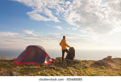 Sunrise in camping day. Alone tourist stands near tent and enjoy beautiful view.
