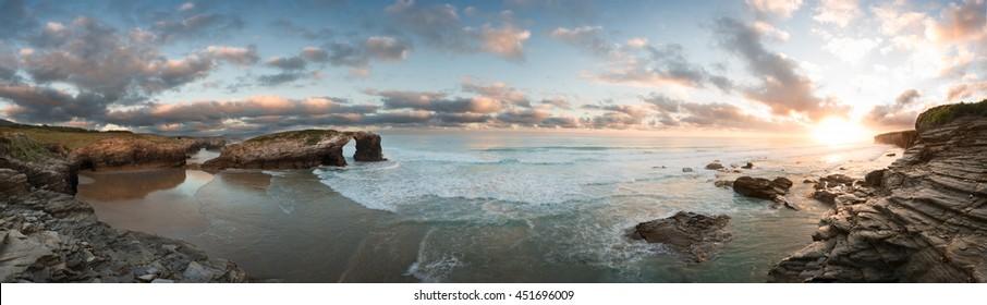 Sunrise at Catedrales beach in Galicia on summer. Sea nature vivid landscape at playa de las catedrales.