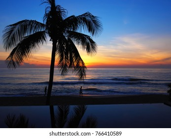 Sunrise in Chaweng beach Koh Samui island, Thailand.reflection of coconut tree in swimming poolSilhouette  man walking on the beach