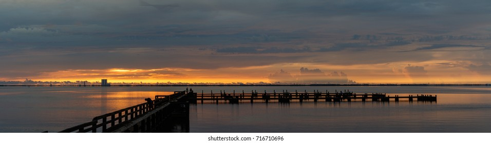 Sunrise with clouds and dock at Banana River, Merritt Island, Florida, USA
