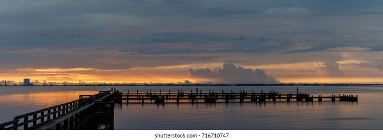 Sunrise with clouds and dock at Banana River, Merritt Island, Florida, USA