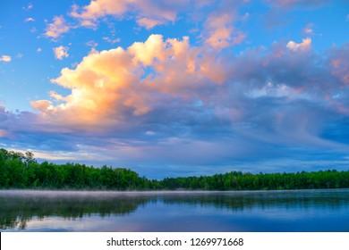 Sunrise clouds over Minnesota summer lake shore reflection.