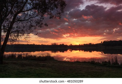 Sunrise colors reflected in Lake Ginninderra with Storm Clouds above the horizon