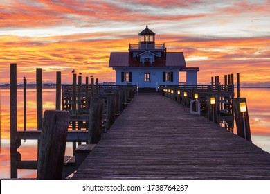 Sunrise colors the sky vivid orange and reflects in the water of Shallowbag Bay at the Roanoke Marshes Lighthouse in downtown Manteo, on the Outer Banks of North Carolina.