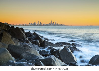 Sunrise colours and Surfers Paradise in the horizon with close up view of the ocean rushing over rocks, viewed from Burleigh Heads Gold Coast.