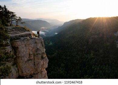 Sunrise at Creux du Van Neuchatel with man standing on steep cliff facing warm sunlight over the ridge