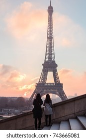 Sunrise in the Eiffel Tower,two girls are taking pictures of the tower