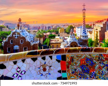 Sunrise famous summer Park Guell designed by Antoni Gaudi located on Carmel Hill, bench covered with tile-shard mosaic, Barcelona, Spain.