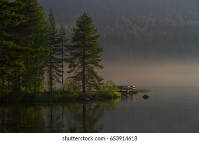 Sunrise in finnish lake with pier and forest and early morning fog. Pines and mirrors of its.