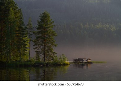 Sunrise in a finnish lake. Pier and forest in a fog finnish summer day.