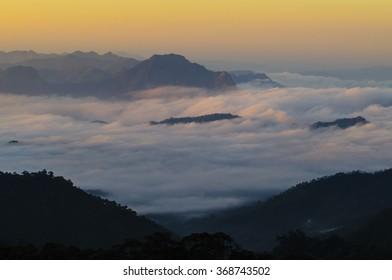 Sunrise A fog covered valley beneath a tall mountain. Thailand