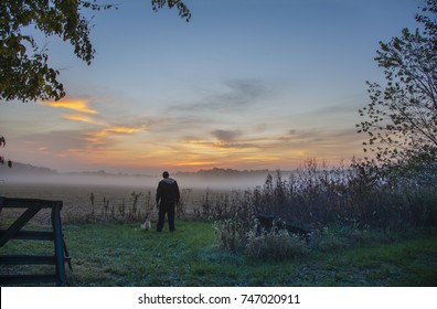 Sunrise with fog on farm in Missouri USA,with farmer and cat looking at land.