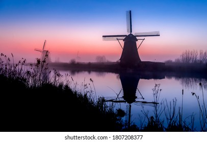 Sunrise fog windmill river reflection. Windmill river sunrise landscape. Windmill sunrise scene. Sunrise windmill river landscape
