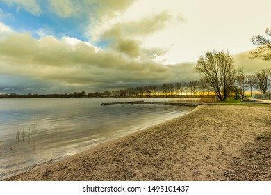 Sunrise at freshwater recreational lake Zegerplas Alphen aan den Rijn with a view of the sandy beach with T-jetty against heavily cloudy skies and breaking sun on the horizon