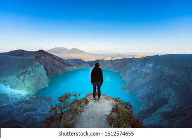 At sunrise girl stand on rock under volcano Kawah Ijen crater. Look at largest in world acid lake, sulphur mine. Popular travel destination, adventure hike on family vacation in Bali, Java, Indonesia