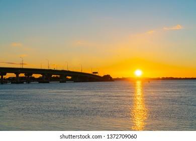 Sunrise  glows across Tauranga harbor with  curving lines of harbor bridge.